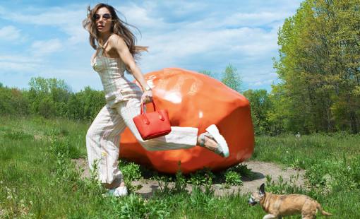 Bianca Jade running with dog at Art Omi Sculpture Park in front of a big orange rock sculpture