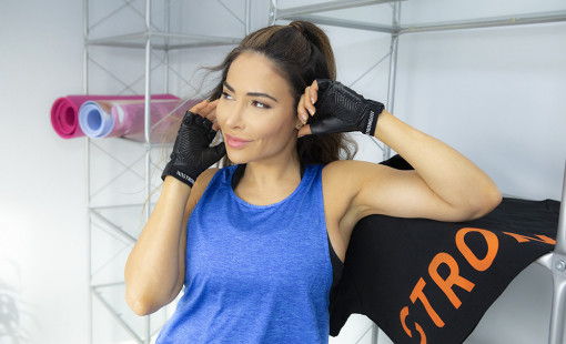Women wearing weight lifting fitness gloves at the gym.