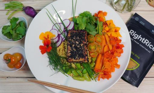 A beautiful presentation of a buddha bowl with rice, colorful vegetables and sesame tofu on a round white plate.