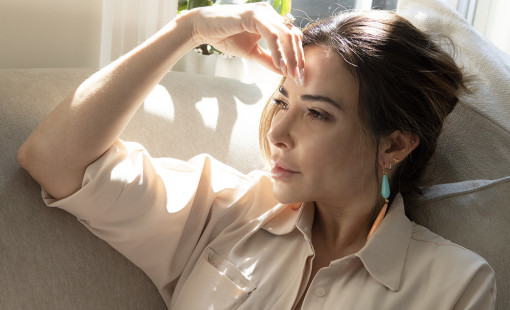 A woman named Bianca Jade touches head and sits pensively on couch.