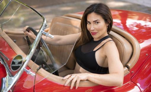 Bianca Jade is driving a Jaguar XK120 Roadster in a cherry red color with tan interior.