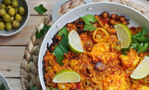 A spanish seafood paella ready to serve and made with green olives, shrimp, squid, parsley, rice and chicken sausage.