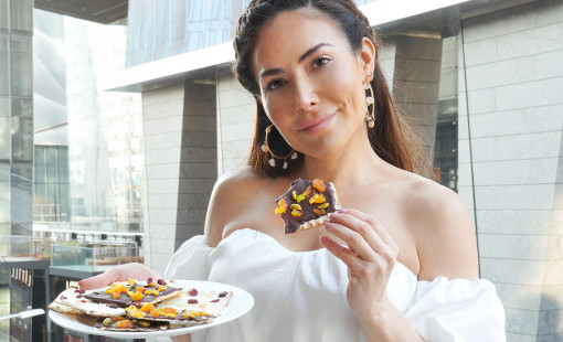 Bianca Jade holds her matzah bark recipe on a plate while about to take a bite of a piece of it.
