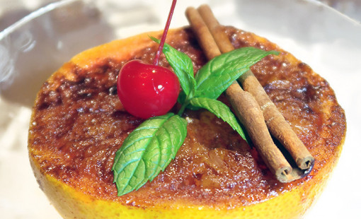 A plated grapefruit brûlée dessert topped with mint leaves, a cherry and a cinnamon stick.