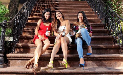 Pretty girls drinking beer on a new york city stoop. Summer of 2020.